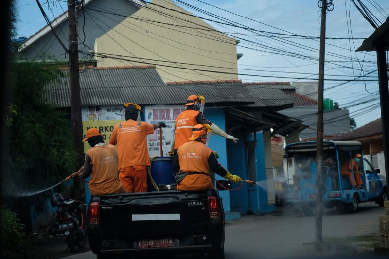 City workers spray a neighborhood with disinfectant in Jakarta on April 1.