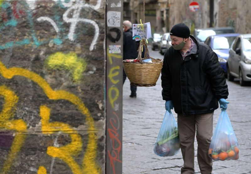 "A man looks at a solidarity basket displayed with a note reading ""Who can, put, who cannot, take"" in one of the deserted streets in the historic center of Naples on April 3."