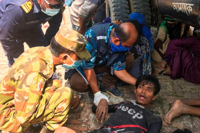 Bangladeshi security personnel attend to emaciated Rohingya refugees following their arrival by boat in Teknaf on April 16, after nearly two months at sea.