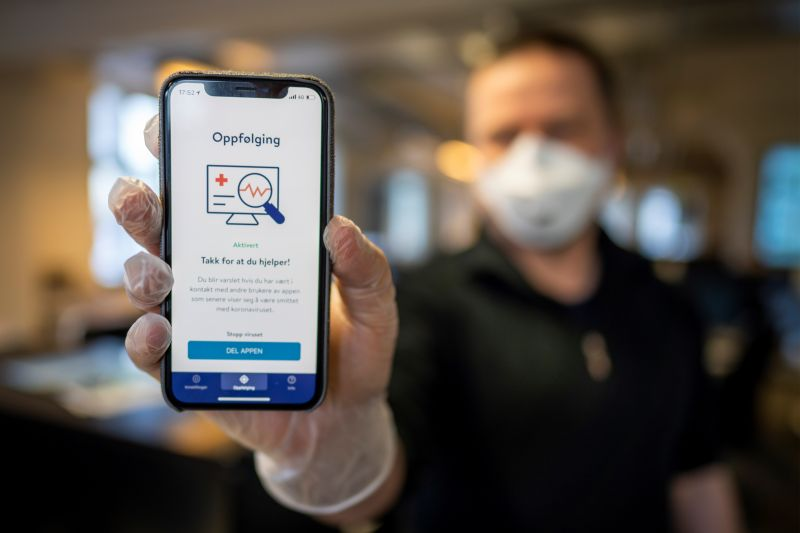 A man holds a smartphone showing a coronavirus tracking and tracing app launched by the Norwegian government, in Oslo on April 17.