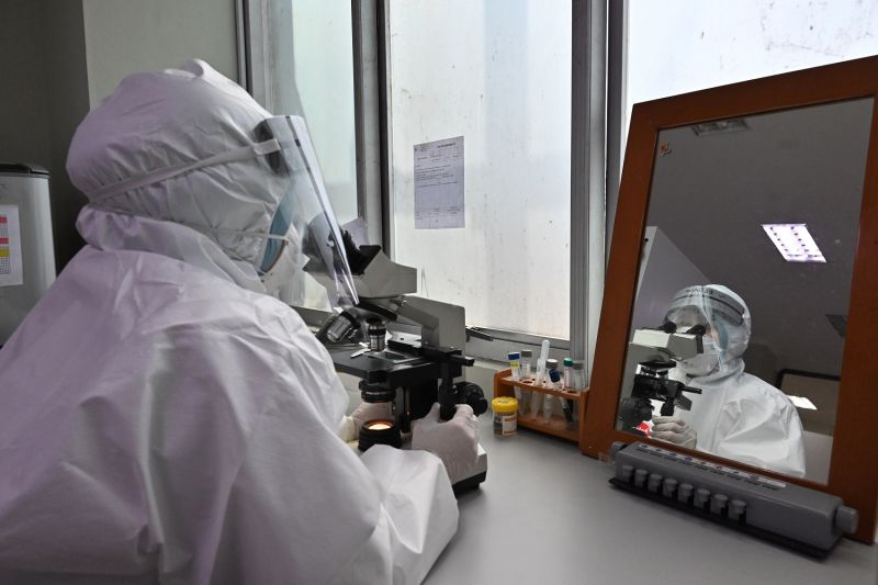 An Indonesian laboratory assistant wearing personal protective equipment uses a microscope in Jakarta on April 22, amid the coronavirus pandemic.