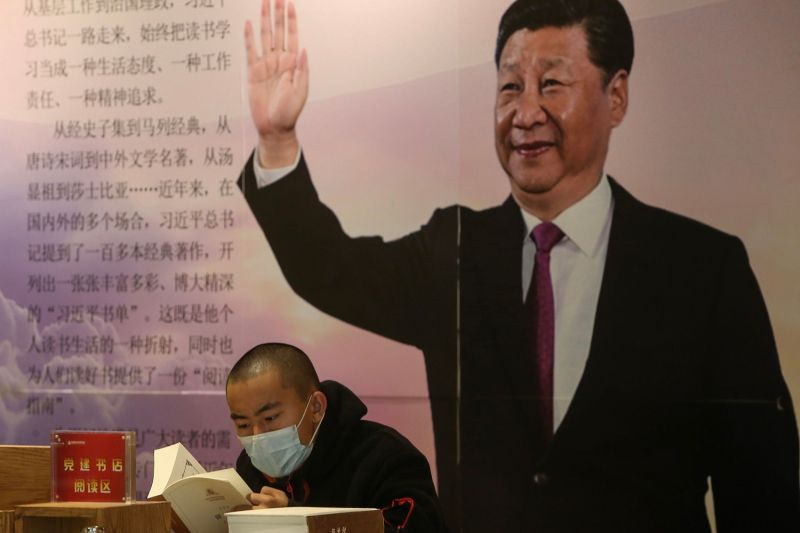 A man reads a book in front of a board with an image of China's President Xi Jinping