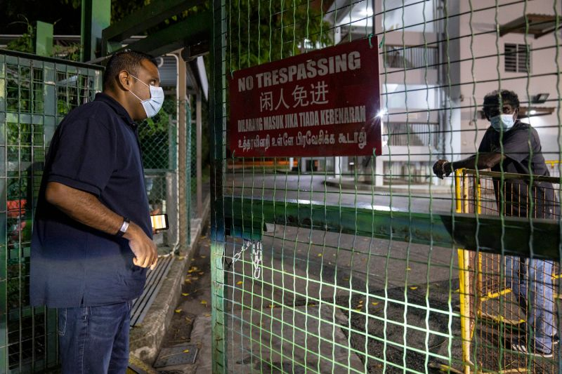 Pastor Samuel Gift Stephen, the founder of the Alliance of Guest Workers Outreach, checks in with a security guard at a factory-converted dormitory as he distributes pre-dawn meals for Muslim migrant workers in Singapore on April 24.