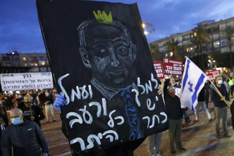 An Israeli protester lifts a placard during a rally in Tel Aviv on April 25, to protest what the demonstrators consider threats to Israeli democracy.