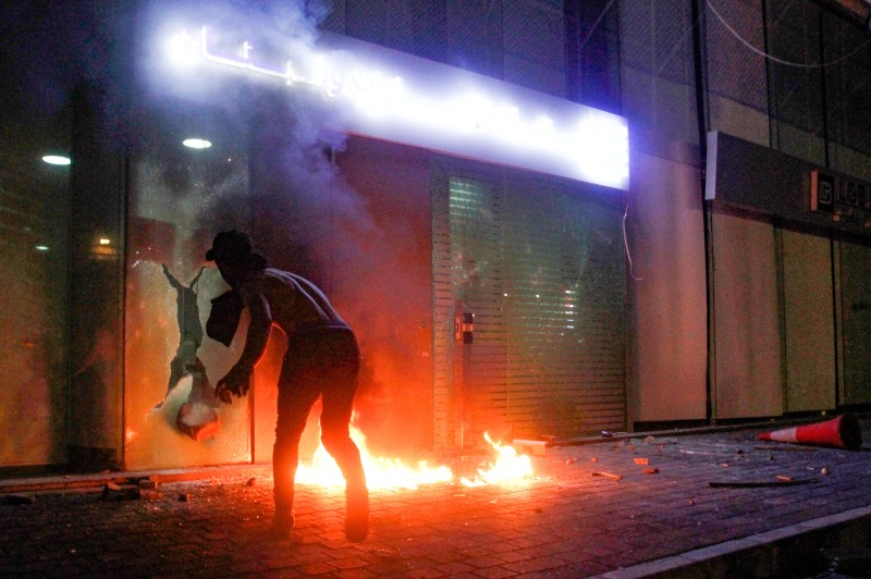 A Lebanese protester launches a bottle bomb toward the entrance of a bank in the southern Lebanese city of Sidon late on April 29, as anger over a spiralling economic crisis in the country reenergized a months-old anti-government movement in defiance of the coronavirus lockdown.