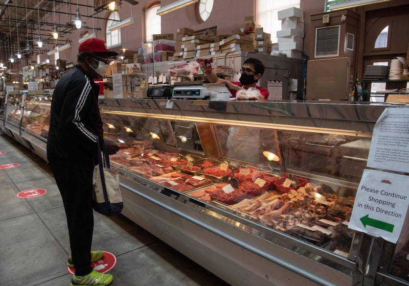 A man purchases meat at Eastern Market in Washington, D.C., on May 5.