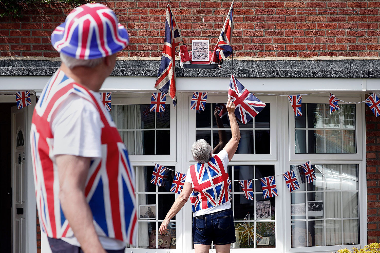 Graham Gillson watches his wife, Sue, untangle a flag outside their home ahead of a two-minute moment of silence to mark the 75th anniversary of VE Day, the end of the Second World War in Europe, in Hartley Wintney, Hampshire, England, on May 8. The two Union cloth flags on the eave flew outside Sue's family home in east London on VE Day 1945. ADRIAN DENNIS/AFP via Getty Images
