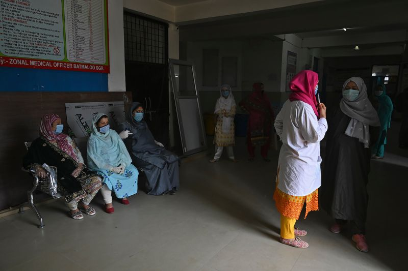 Pregnant women sit as they wait for their turn at a coronavirus testing center