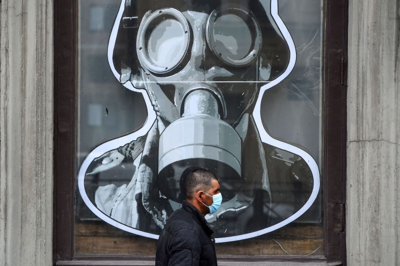 A man wearing a protective face mask walks past a military store in Saint Petersburg on May 11, 2020.