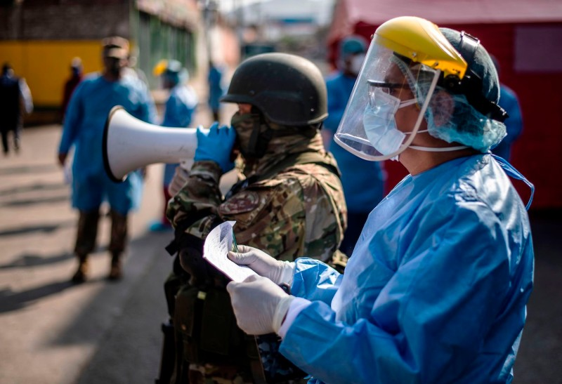 A soldier speaks on a megaphone next to a worker from the Health Ministry during an operation to test employees of the Ciudad de Dios market for the coronavirus in Lima on May 11.
