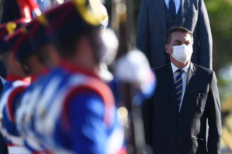 Brazilian President Jair Bolsonaro wears a face mask as he attends a flag-raising ceremony before a ministerial meeting at the Alvorada Palace in Brasília on May 12.