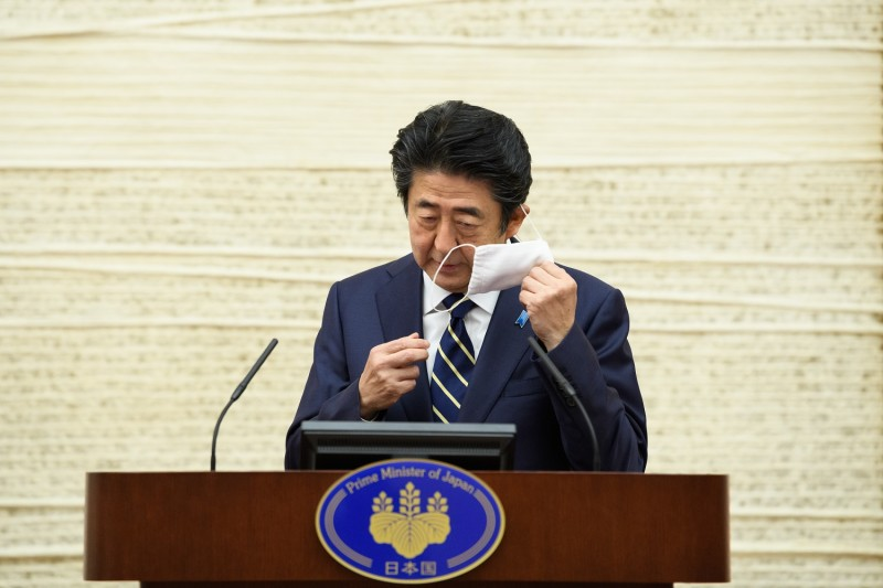 Japanese Prime Minister Shinzo Abe takes off his face mask before speaking during a press conference at the prime minister's office in Tokyo on May 14.