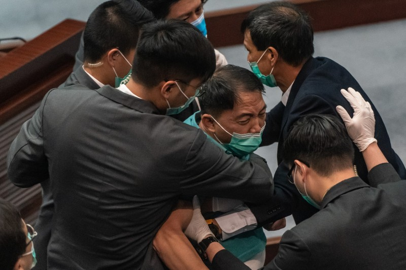 The pro-democracy lawmaker Wu Chi-wai is removed by security during a scuffle with pro-Beijing lawmakers at the House Committee's election of vice chairpersons, presided by pro-Beijing lawmaker Starry Lee Wai-king at the Legislative Council  in Hong Kong on May 22.