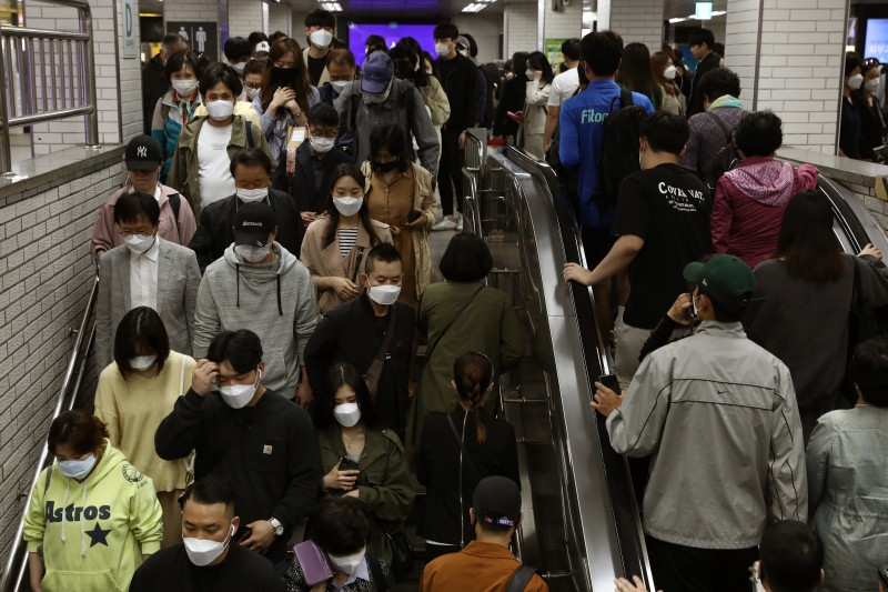 Seoul commuters wear protective masks as they crowd on an escalator and stairs after getting off the subway during rush hour on May 11.