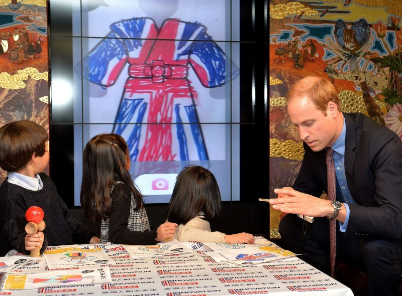 Prince William of Britain scans in a drawing of himself onto a screen so he can make a cartoon character of himself dressed in a traditional Japanese costume during his visit to Tsutaya bookshop in Tokyo on Feb. 28, 2015.