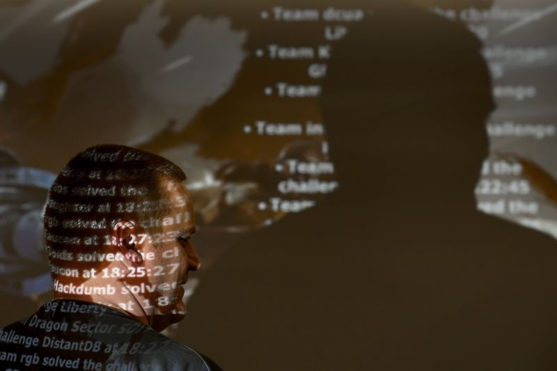 A participant stands near a screen during the ethical hacking contest Insomni'hack in Geneva on March 21, 2014.