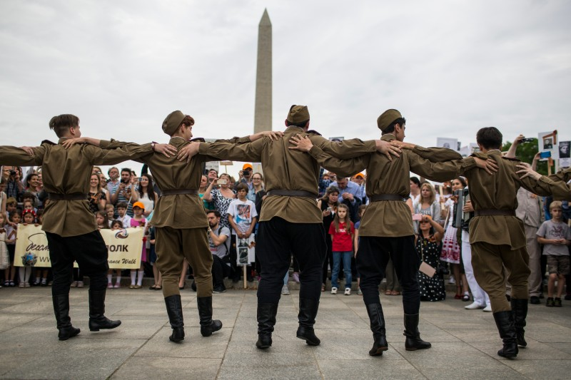 "Demonstrators dance at the World War II Memorial during an ""Immortal Regiment"" Remembrance Walk to mark the 73rd anniversary of Victory in Europe Day in Washington on May 5, 2018."