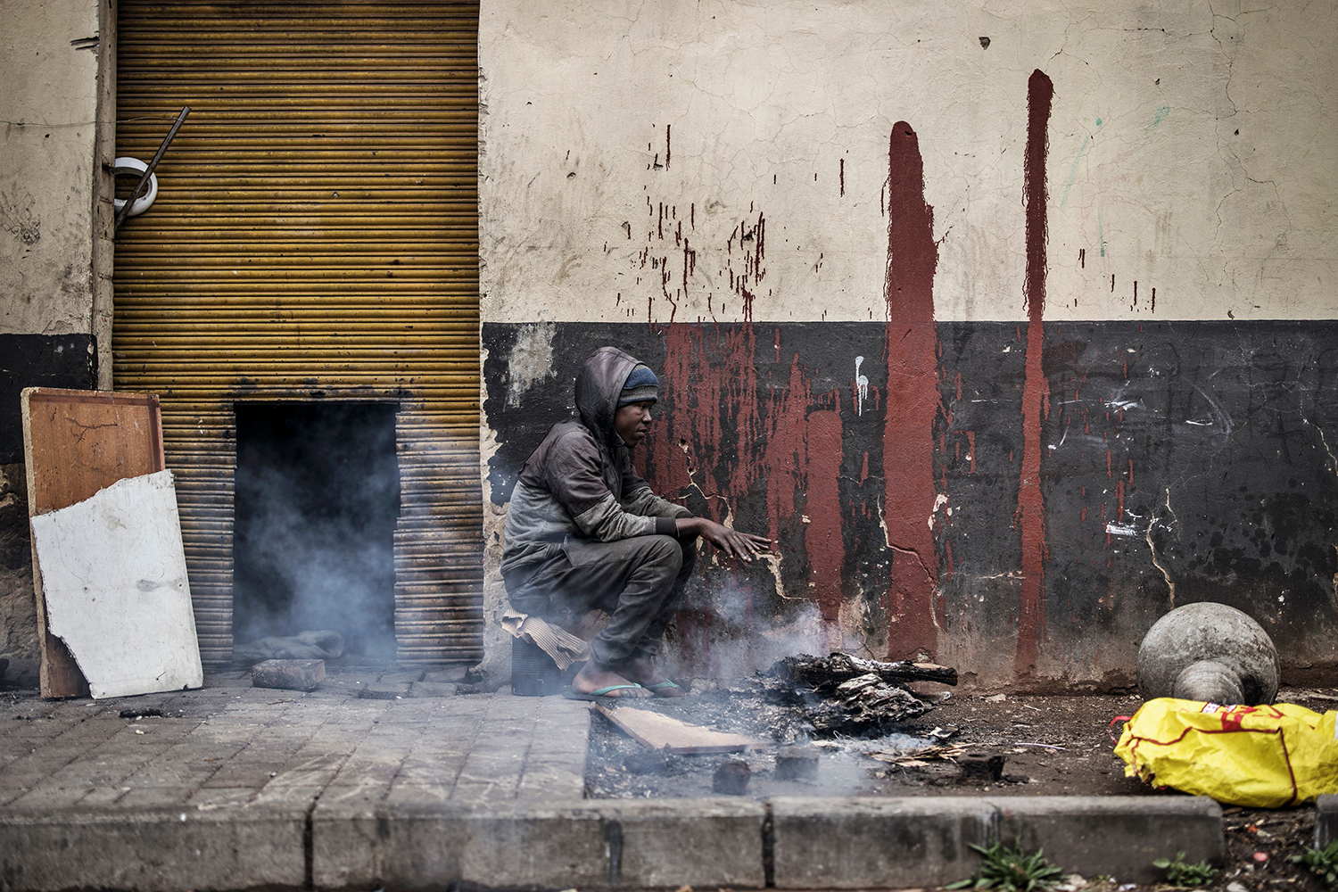 A homeless man warms up by burning wood in Johannesburg, South Africa, on April 28. MARCO LONGARI/AFP via Getty Images