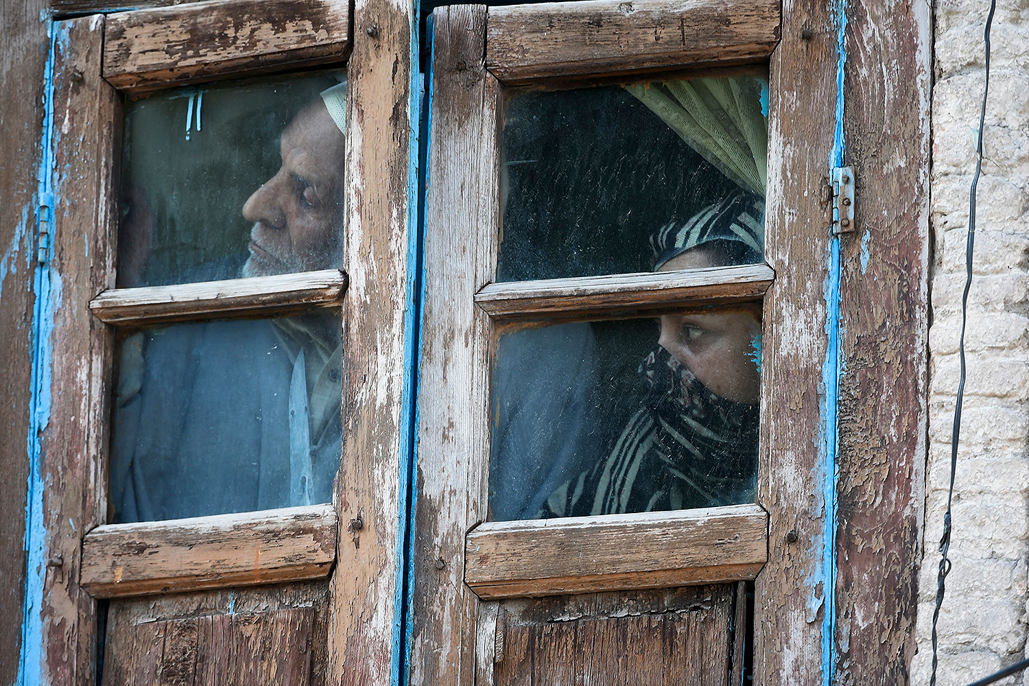 Residents watch from their window as a gun battle takes place between suspected militants and government forces in Srinagar, India, on May 19. Two Kashmir militants, including a key rebel leader, were killed in the 12-hour gun battle. TAUSEEF MUSTAFA/AFP via Getty Images
