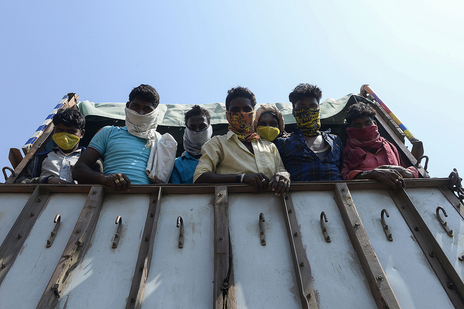 Migrant workers ride in a truck on the outskirts of Hyderabad, India, on May 15 as they return to their hometowns after the government eased a nationwide lockdown. NOAH SEELAM/AFP via Getty Images