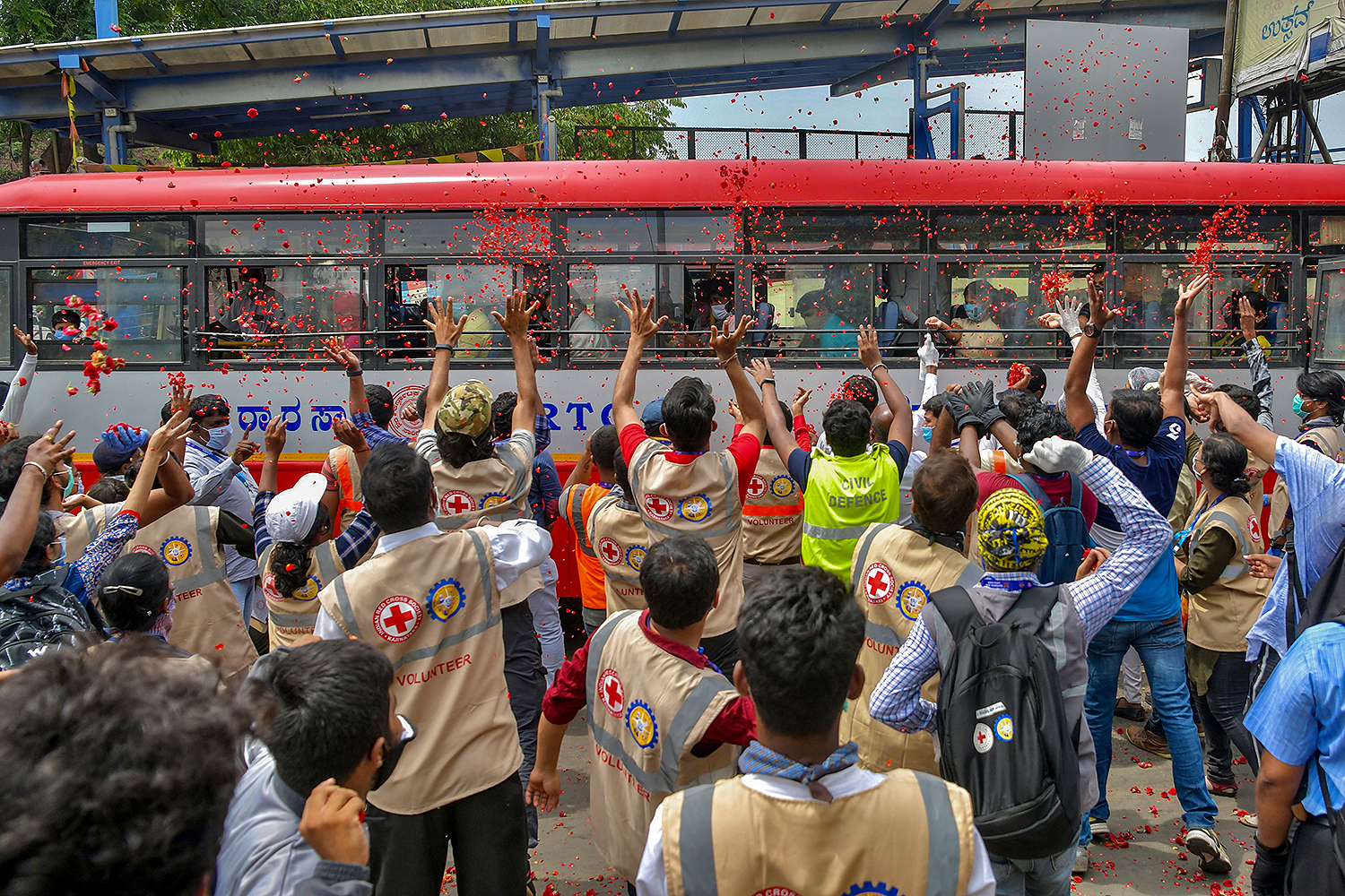 Volunteers with the Indian Red Cross and other nongovernmental organizations in Bangalore throw flower petals on a bus transporting migrant workers and families to their hometowns after the government eased a nationwide lockdown May 7. MANJUNATH KIRAN/AFP via Getty Images