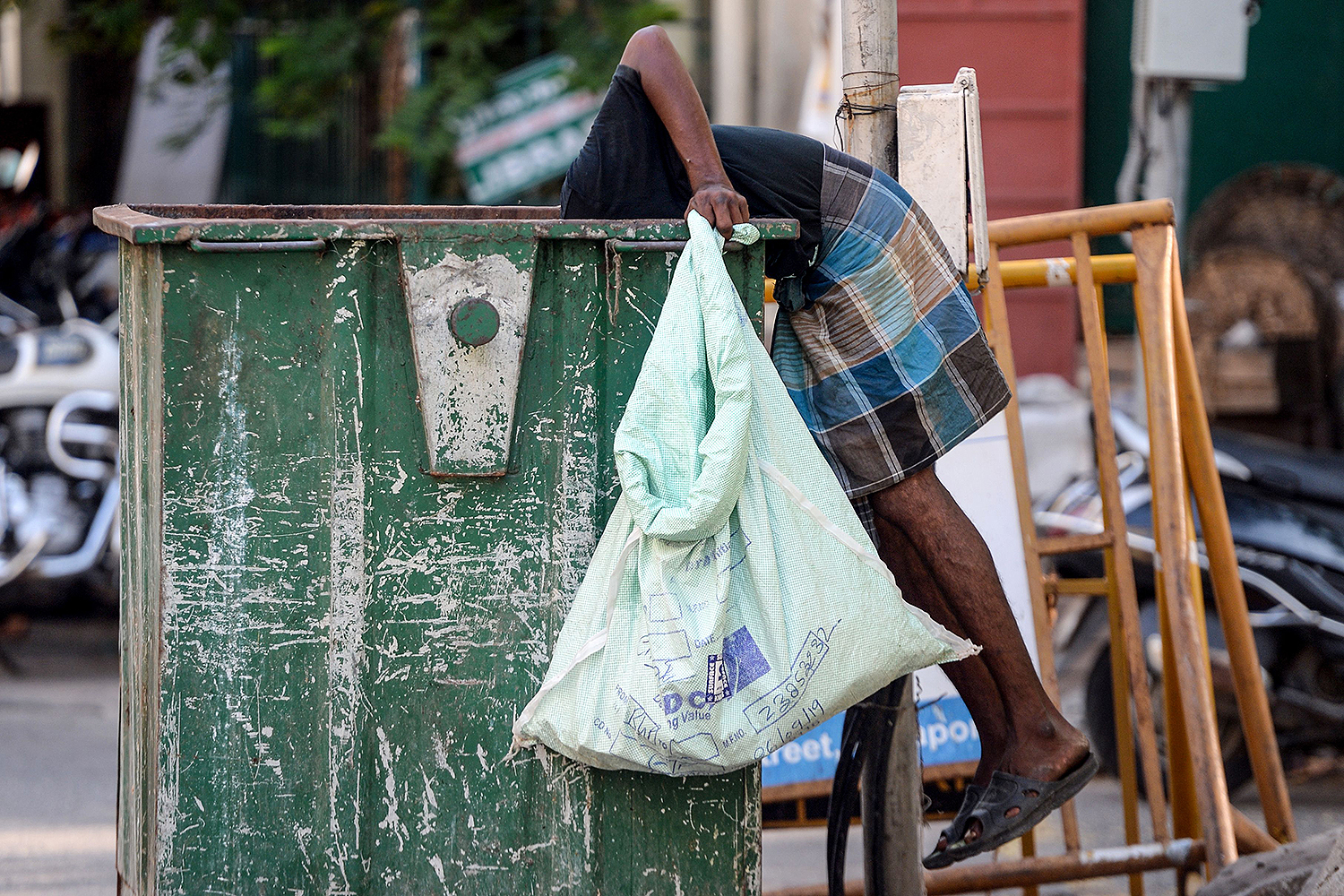 A man checks a waste bin for reusable items during a government-imposed lockdown in Chennai, India, on April 24. ARUN SANKAR/AFP via Getty Images