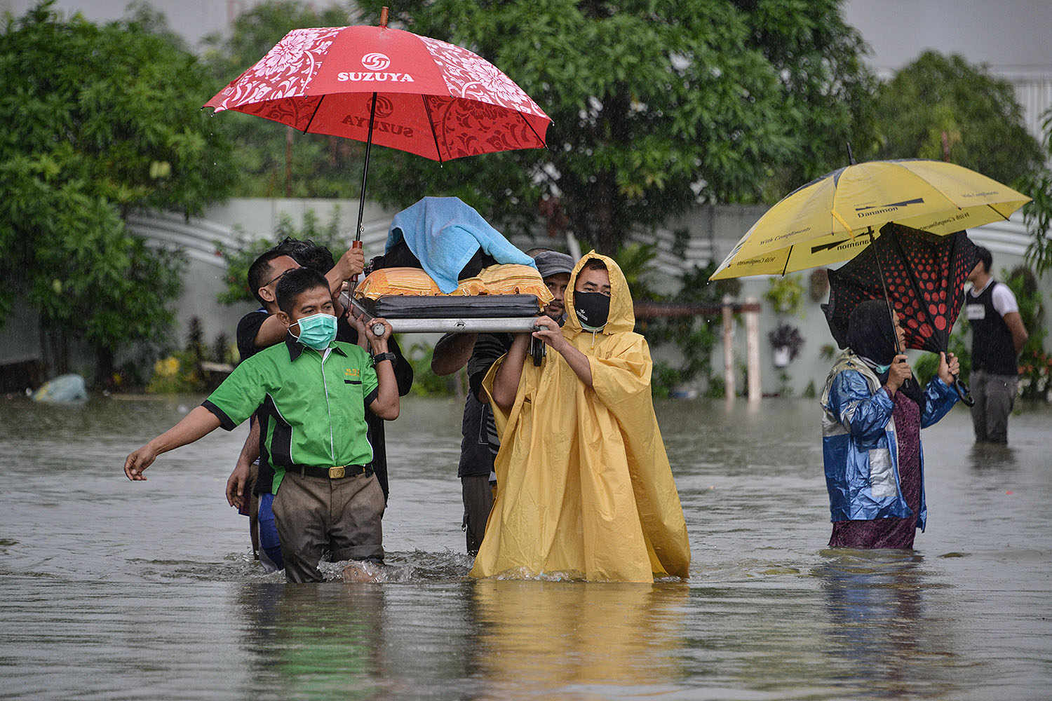 Medical workers evacuate a woman through a flooded residential area caused by heavy rain in Banda Aceh, Indonesia, on May 8. CHAIDEER MAHYUDDIN/AFP via Getty Images