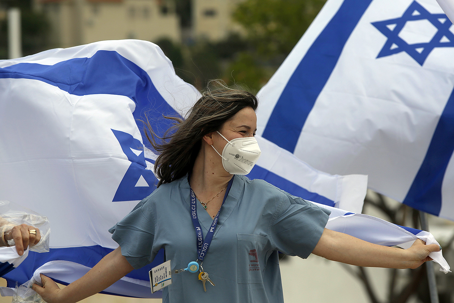Health care workers at Ziv Medical Center in the northern city of Safed wave flags as Israeli Air Force jets fly over the hospital to mark Israel's Independence Day (Yom Ha'atzmaut) on April 29. JALAA MAREY/AFP via Getty Images