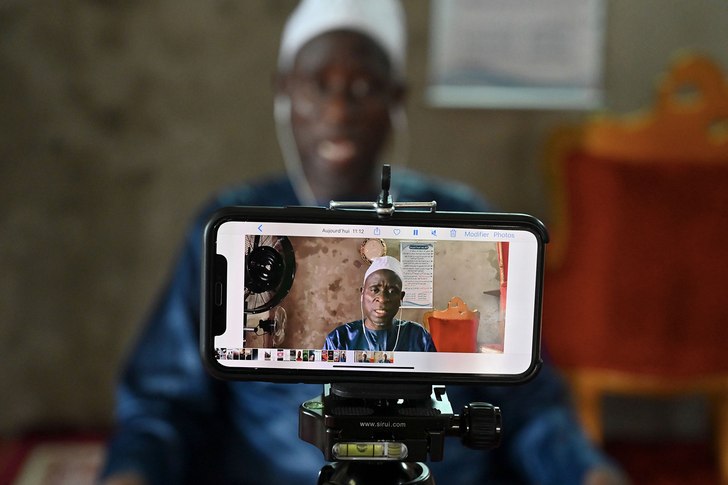 An imam on May 1 records his preaching of the Friday prayer—to be broadcast on social networks—in Abidjan, Ivory Coast, where mosques and churches are closed because of the pandemic. ISSOUF SANOGO/AFP via Getty Images