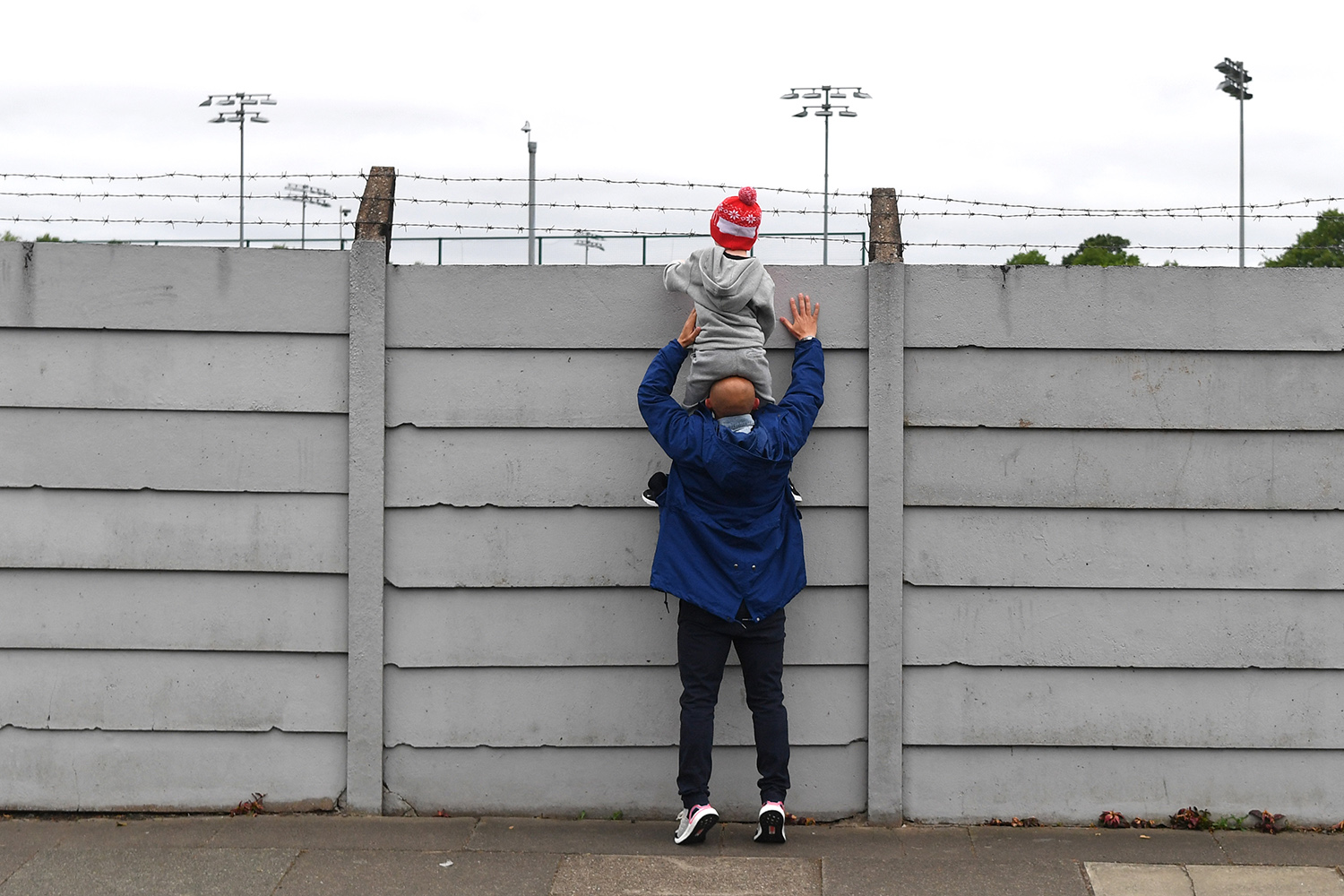 A father holds up his son so he can see over the fence at Melwood training ground, a playing field for the Liverpool Football Club, as players resume training May 19 in Liverpool. PAUL ELLIS/AFP via Getty Images