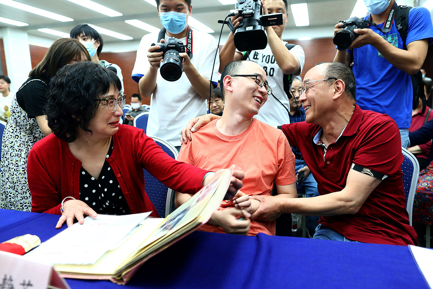 Mao Yin (center) is reunited with his mother, Li Jingzhi, and father, Mao Zhenping, in Xian, China, on May 18. Mao Yin was kidnapped as a toddler in 1988; police used facial recognition technology to track him down. STR/AFP via Getty Images