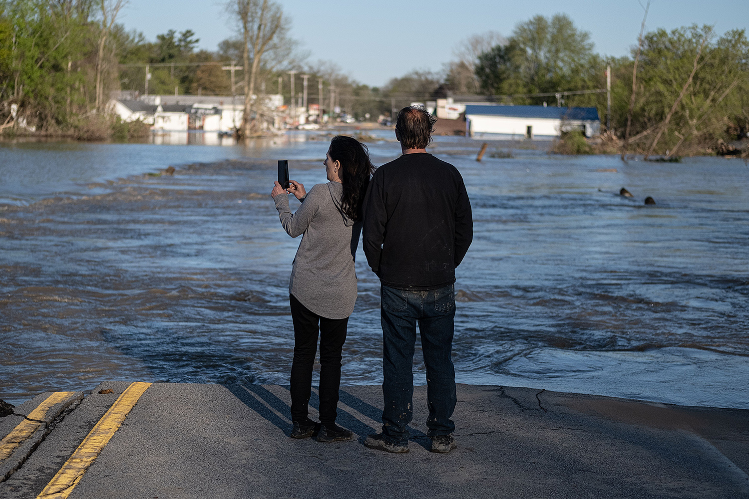 Residents look out at the floodwaters in Sanford, Michigan, on May 20. More than 10,000 people were evacuated after two dams failed following heavy rain. SETH HERALD/AFP via Getty Images