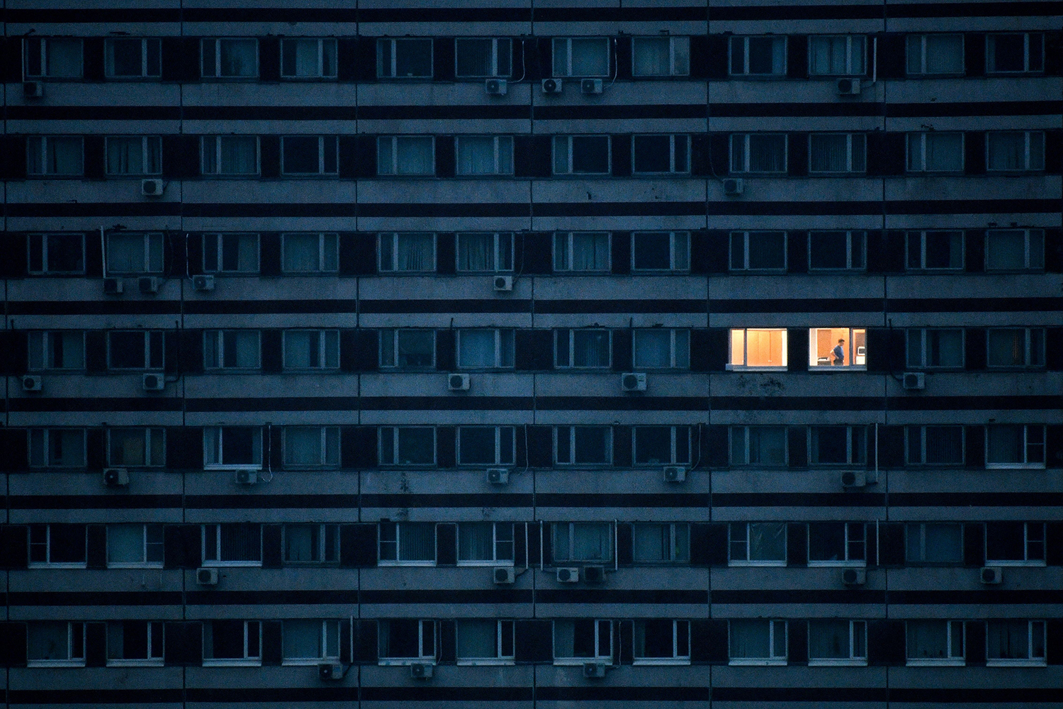 A man is pictured in an illuminated apartment on the outskirts of Moscow on May 4 during the government lockdown. KIRILL KUDRYAVTSEV/AFP via Getty Images