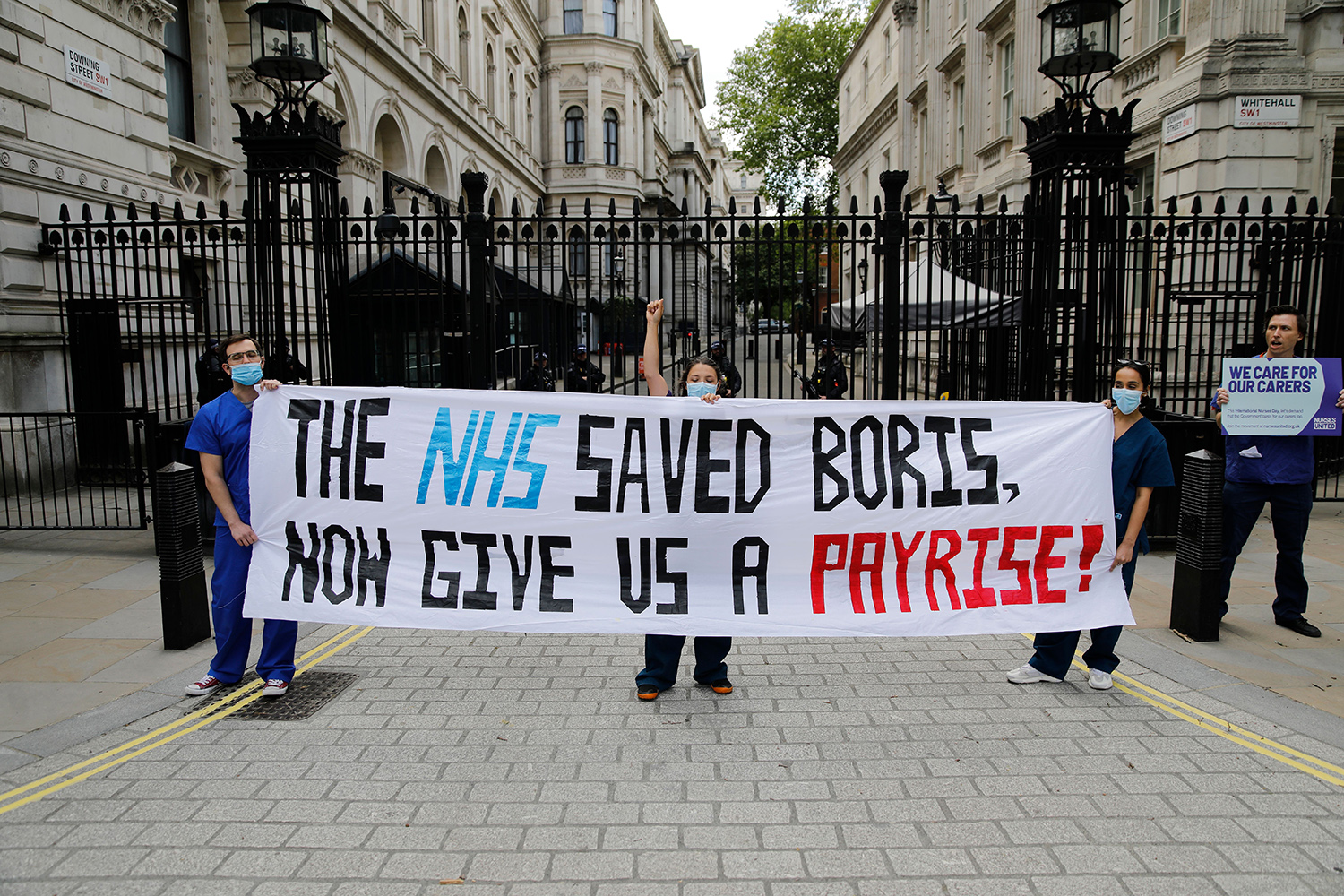 Nurses who work at central London hospitals call for improved conditions and pay as they protest outside Downing Street on International Nurses Day, May 13. TOLGA AKMEN/AFP via Getty Images