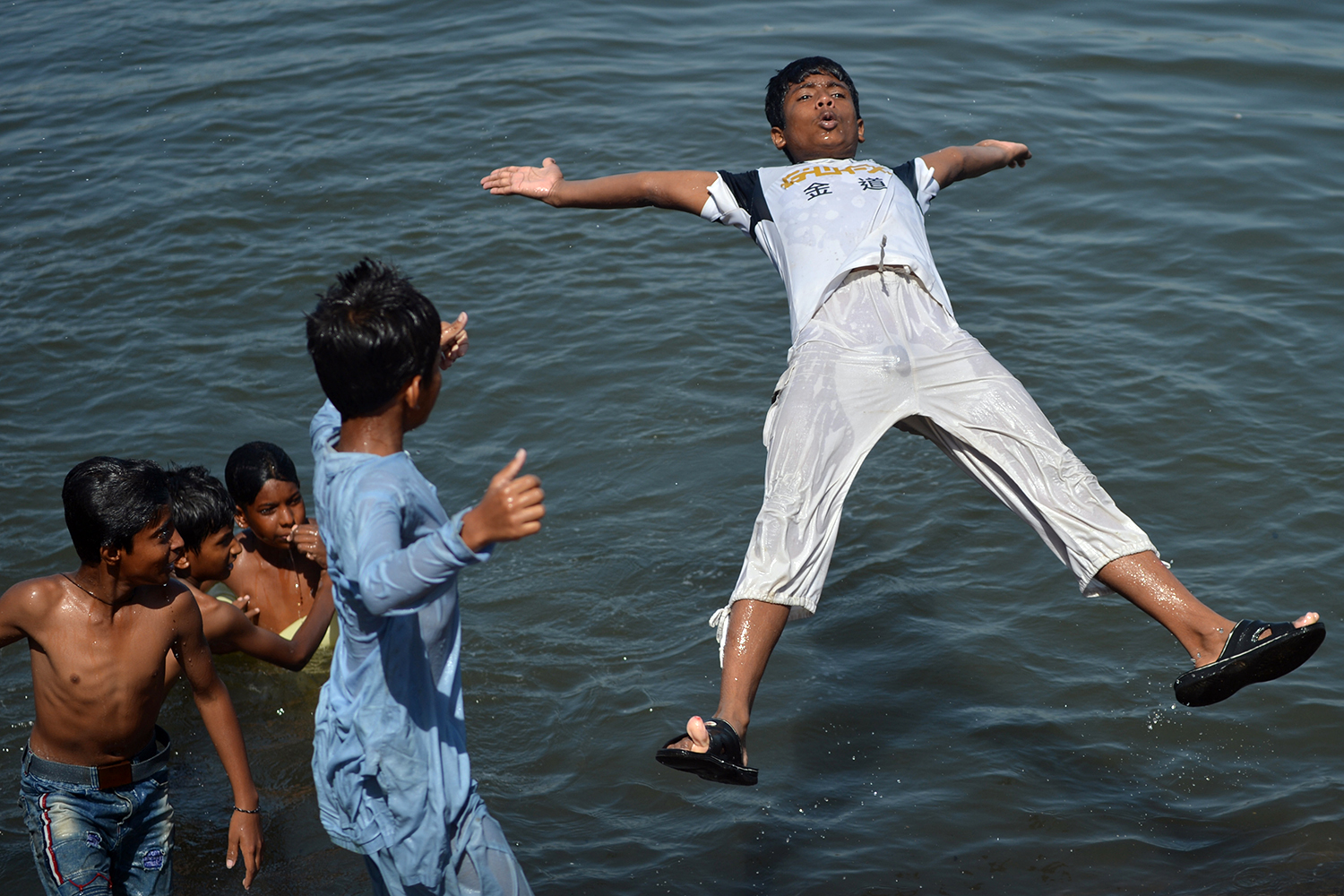 A young boy jumps into the Arabian Sea along a street in Karachi, Pakistan, on April 29. RIZWAN TABASSUM/AFP via Getty Images
