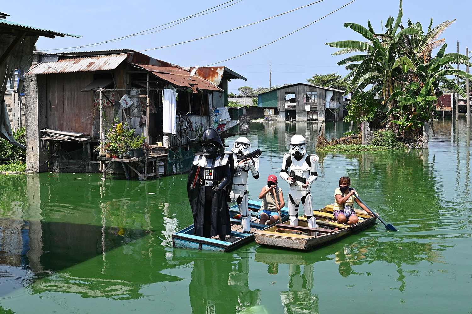 Local youth representatives dressed Stormtroopers and Darth Vader patrol in a wooden boat around a submerged village in Manila, Philippines, on May 6 to remind residents to stay at home during the enhanced community quarantine. TED ALJIBE/AFP via Getty Images)