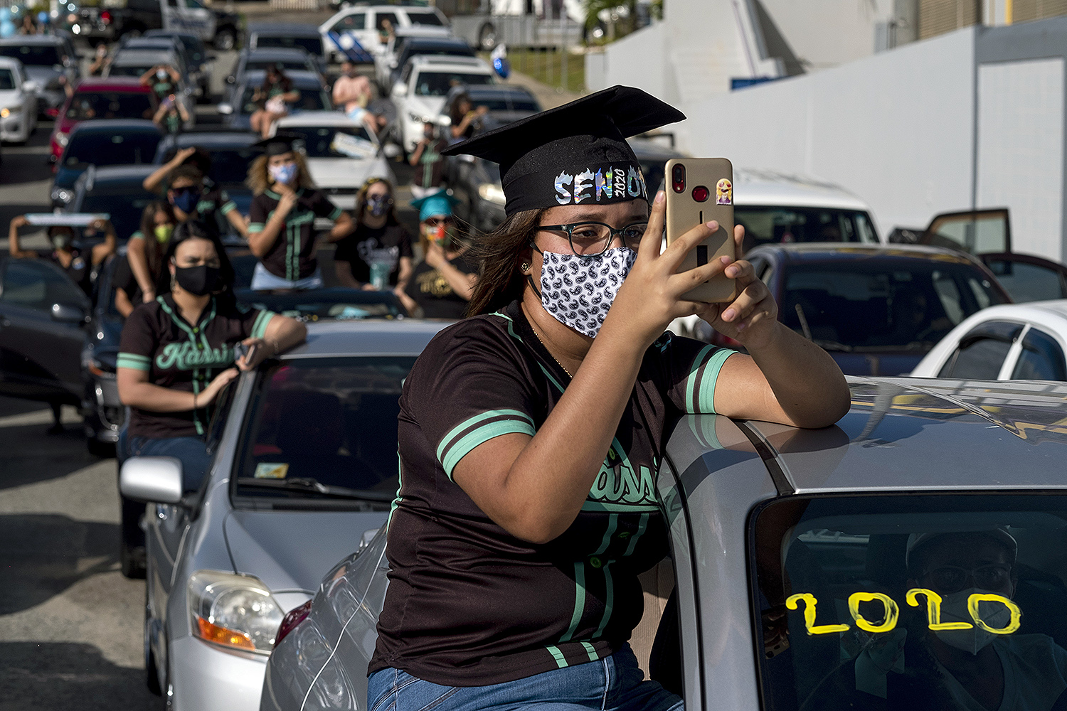Graduating students from Ramon Power Y Giralt High School take part in a symbolic ceremony from their cars in a parking lot in Las Piedras, Puerto Rico, on May 13. RICARDO ARDUENGO/AFP via Getty Images