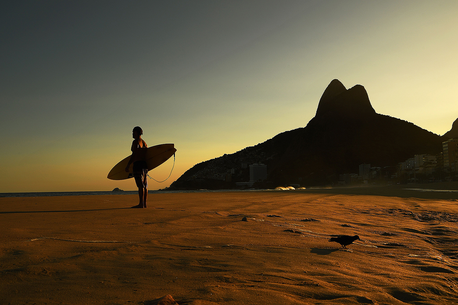 A surfer looks out at his friends in the sea on an empty Ipanema Beach in Rio de Janeiro on April 28. Rio's famous beaches were closed to the public—except for surfers. CARL DE SOUZA/AFP via Getty Images