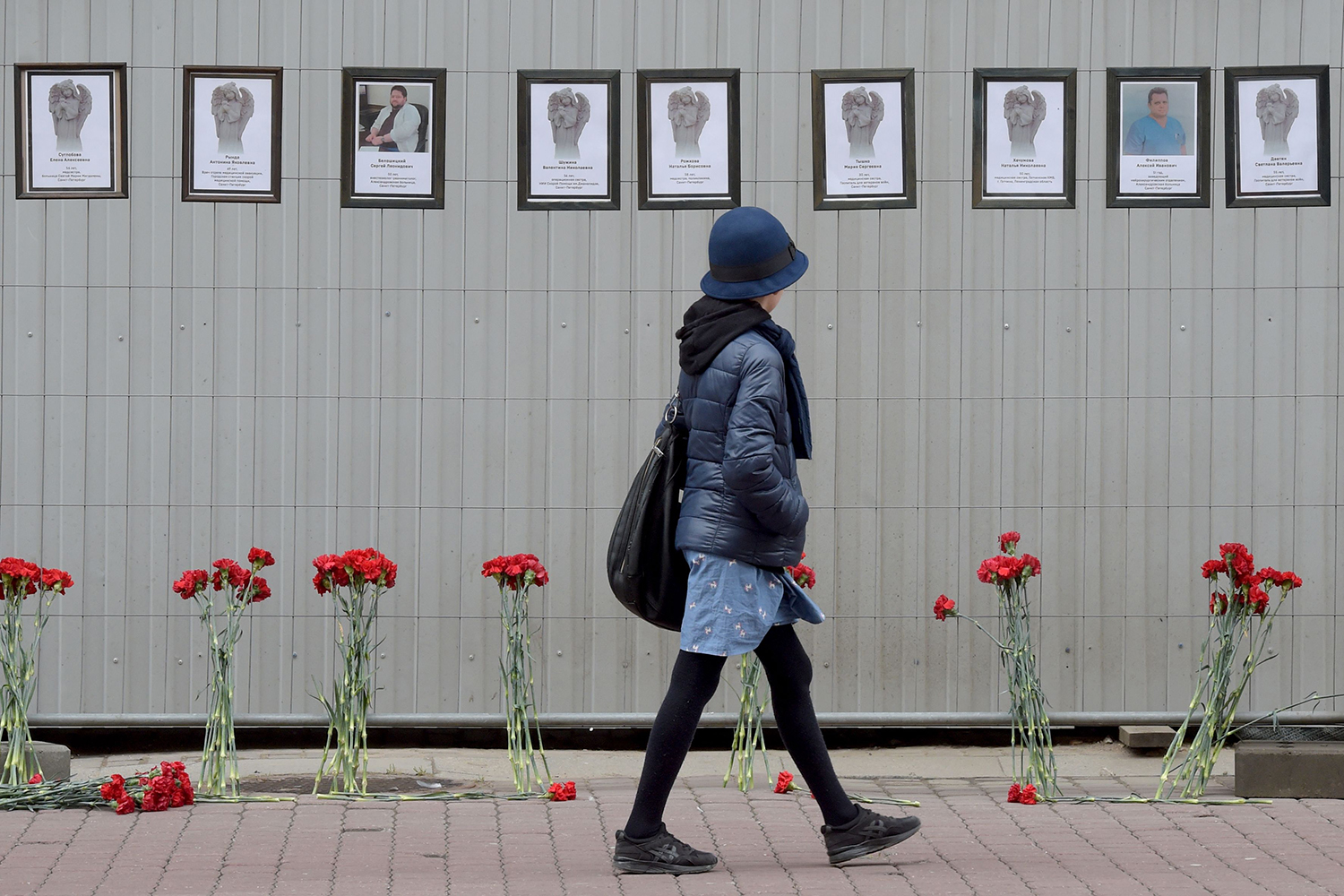 A woman walks past a makeshift memorial for medical workers who have died from COVID-19, set up outside the local health department in Saint Petersburg, Russia, on April 28. OLGA MALTSEVA/AFP via Getty Images