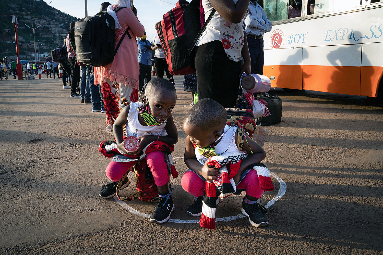People stand in circles to adhere to social distancing measures as they wait for a bus at Nyabugogo bus station in Kigali, Rwanda, on May 4, the first day that the nationwide coronavirus lockdown was partially lifted. SIMON WOHLFAHRT/AFP via Getty Images