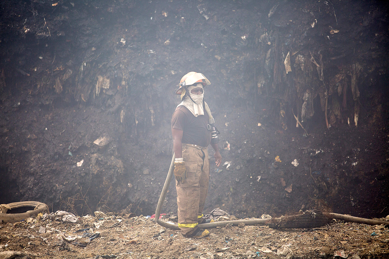 A firefighter takes a break from putting out a fire that had been burning for four days at the Duquesa landfill in Santo Domingo on May 2. The fire was the second to occur in less than a month—attributed to the high temperatures in the Dominican Republic, combined with gas generated by the waste. ERIKA SANTELICES/afp/AFP via Getty Images