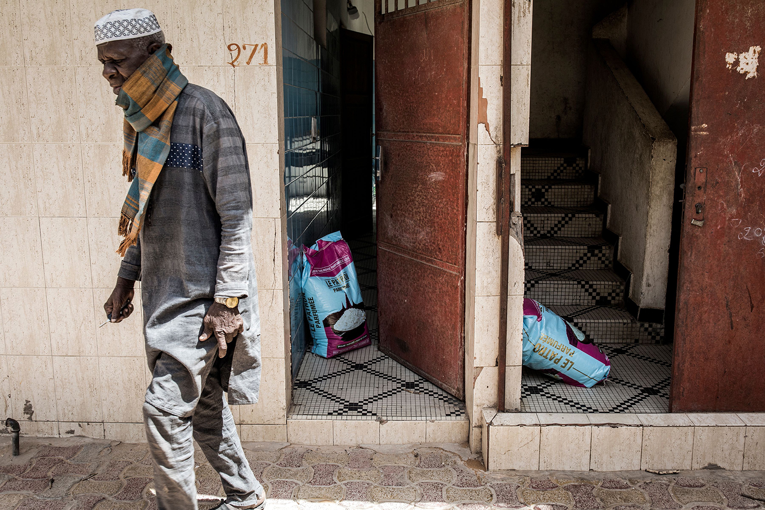 A Senegalese man walks past sacks of rice left at doors in Dakar for those in need May 7. JOHN WESSELS/AFP via Getty Images