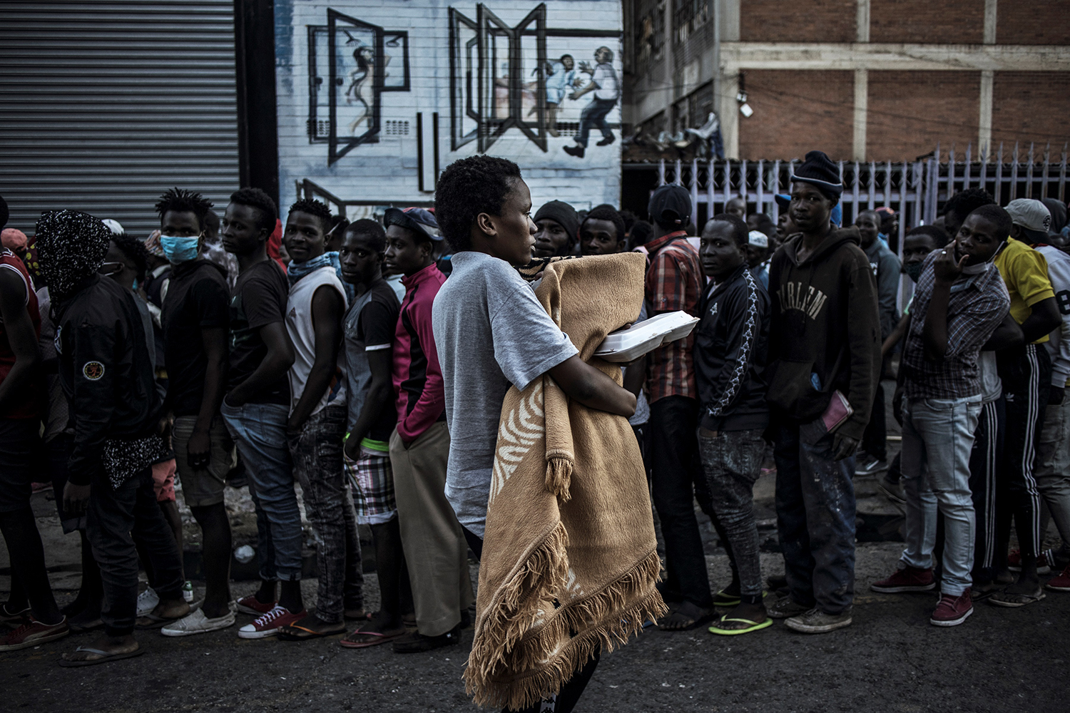 A man walks past people lined up to receive food distributed by a local Muslim welfare organization in the Kwa Mai Mai area of the Johannesburg, South Africa, on May 5. MARCO LONGARI/AFP via Getty Images