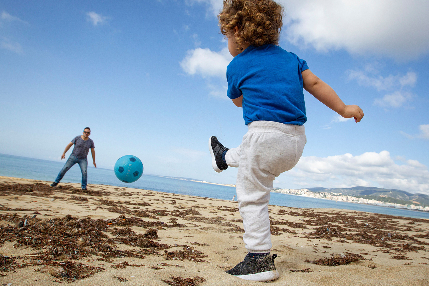 A child plays ball with his father at Can Pere Antoni Beach in Palma de Mallorca, Spain, on April 26. After six weeks stuck at home, Spain's children were being allowed out to run, play, or go for a walk as the government eased one of the world's toughest coronavirus lockdowns. JAIME REINA/AFP via Getty Images