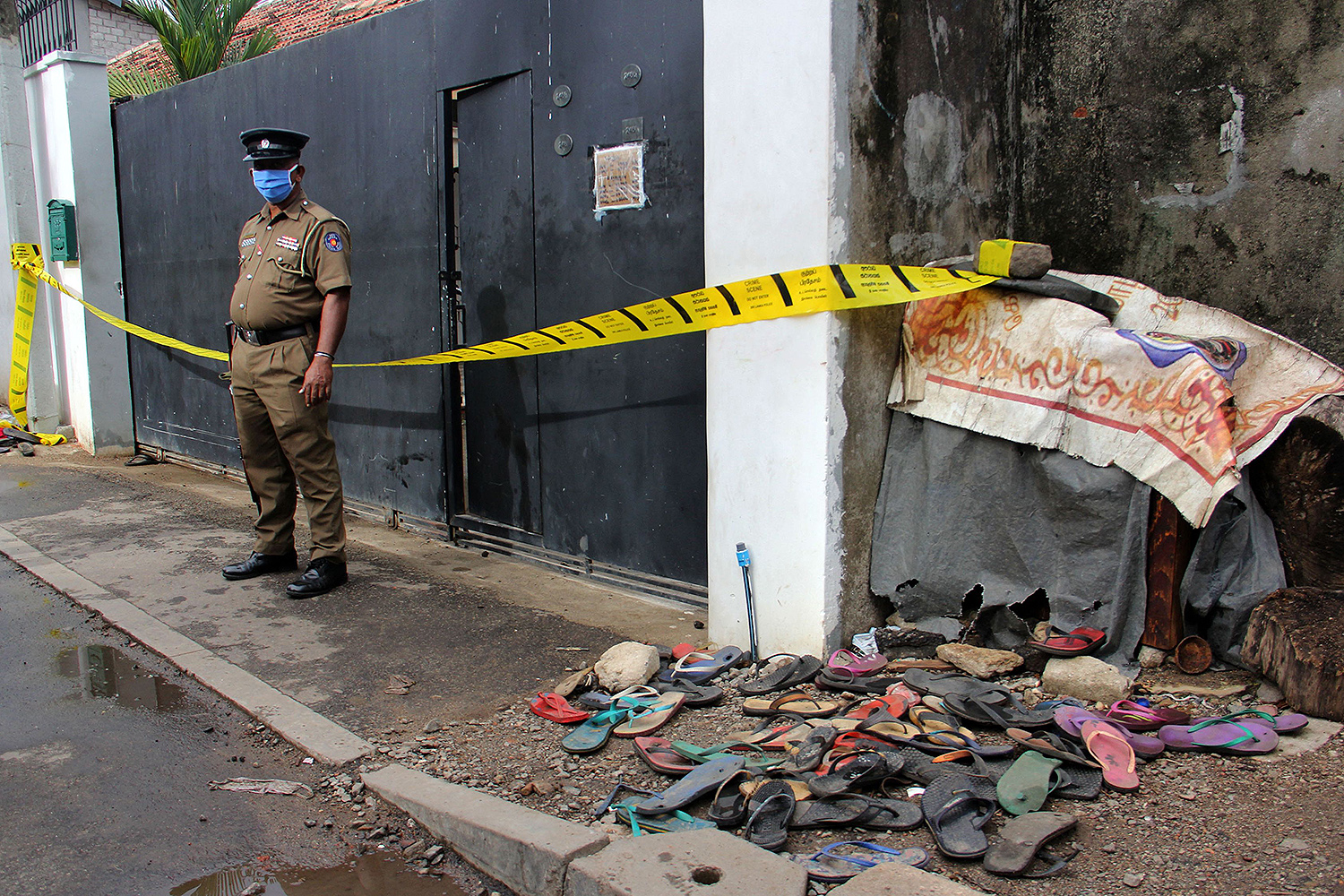 A policeman stands guard outside a warehouse in Colombo, Sri Lanka, on May 21 after three women were crushed to death during a cash distribution for residents affected by the coronavirus lockdown. STR/AFP via Getty Images