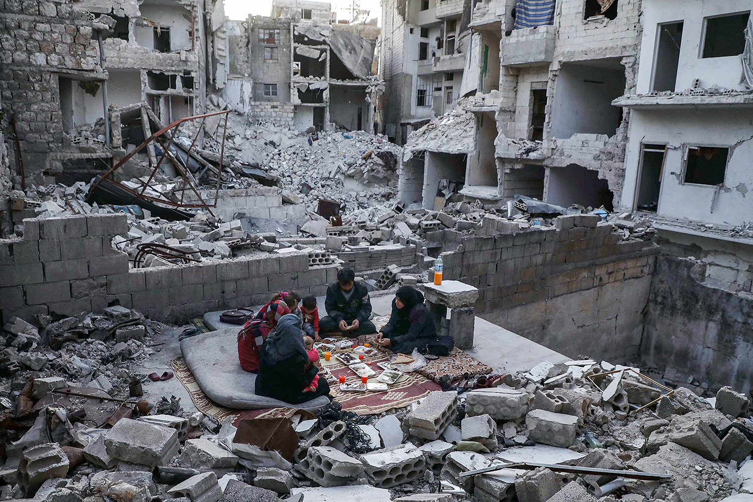 Members of a displaced Syrian family break their Ramadan fast at a sunset Iftar meal in the midst of the rubble of their destroyed home in Ariha, in the Idlib province, on May 4. The family returned to the town for one day after fleeing during a previous military assault by Syrian government forces and their allies. AAREF WATAD/AFP via Getty Images