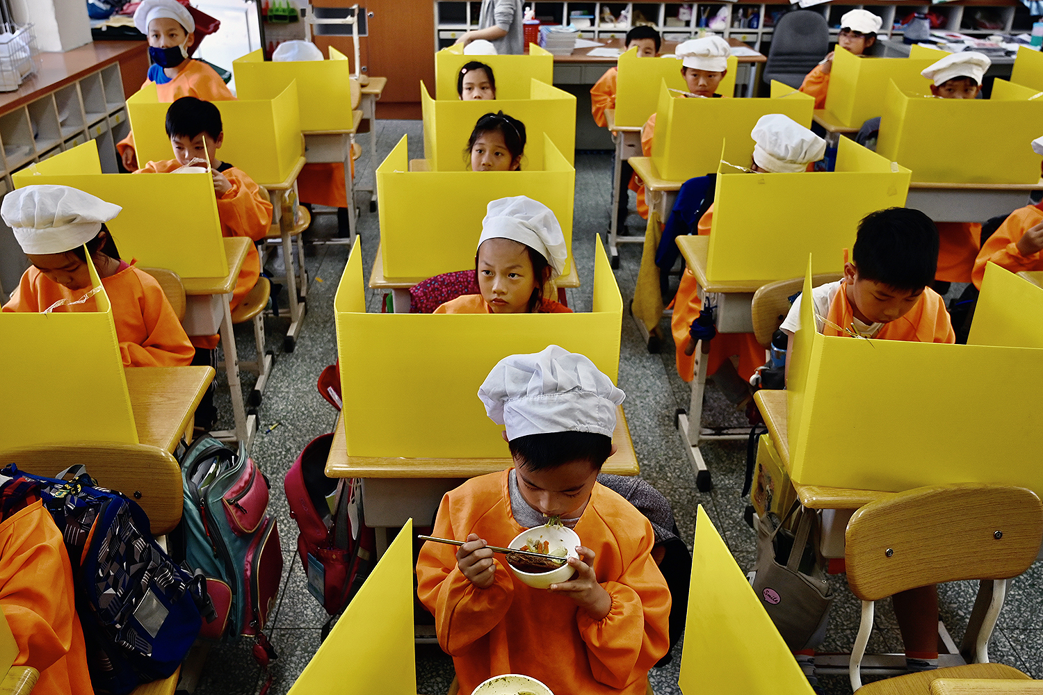 Students eat lunch on desks with plastic partitions as a preventive measure to curb the spread of the coronavirus at Dajia Elementary School in Taipei, Taiwan, on April 29. SAM YEH/AFP via Getty Images)