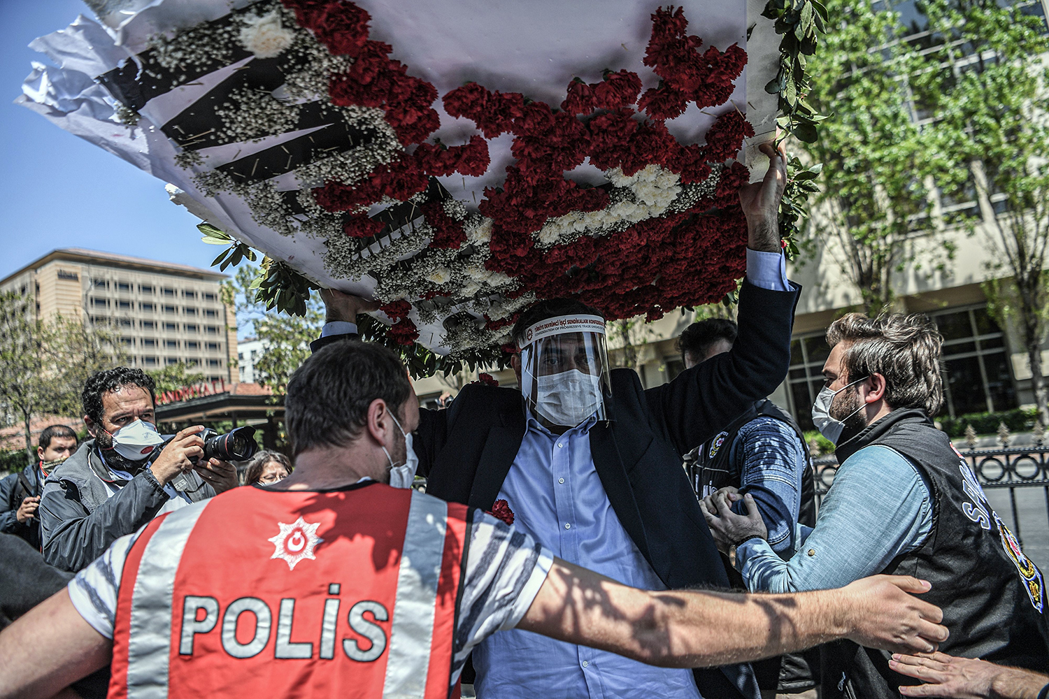 Ali Seker, a lawmaker of the Turkish opposition Republican People's Party, is blocked by police as he carries a wreath in Istanbul on May 1 during a march to mark May Day in defiance of the government lockdown. OZAN KOSE/AFP via Getty Images
