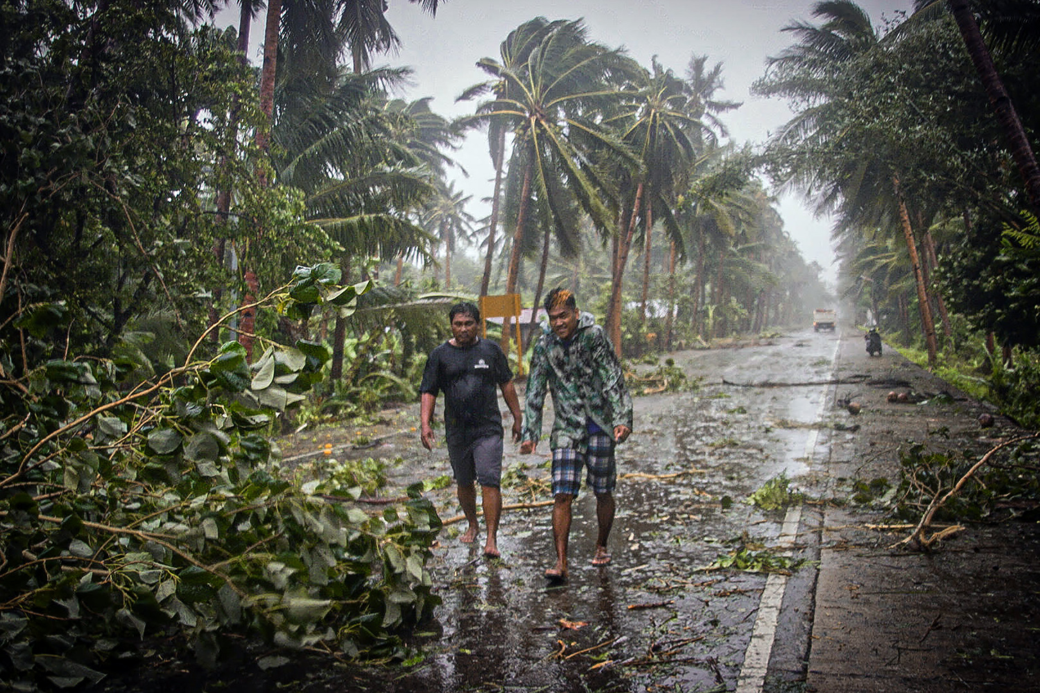As Typhoon Vongfong makes landfall in central Philippines on May 14, residents brave the rains and strong wind on a walk along a highway in Can-avid, Samar. ALREN BERONIO/AFP via Getty Images