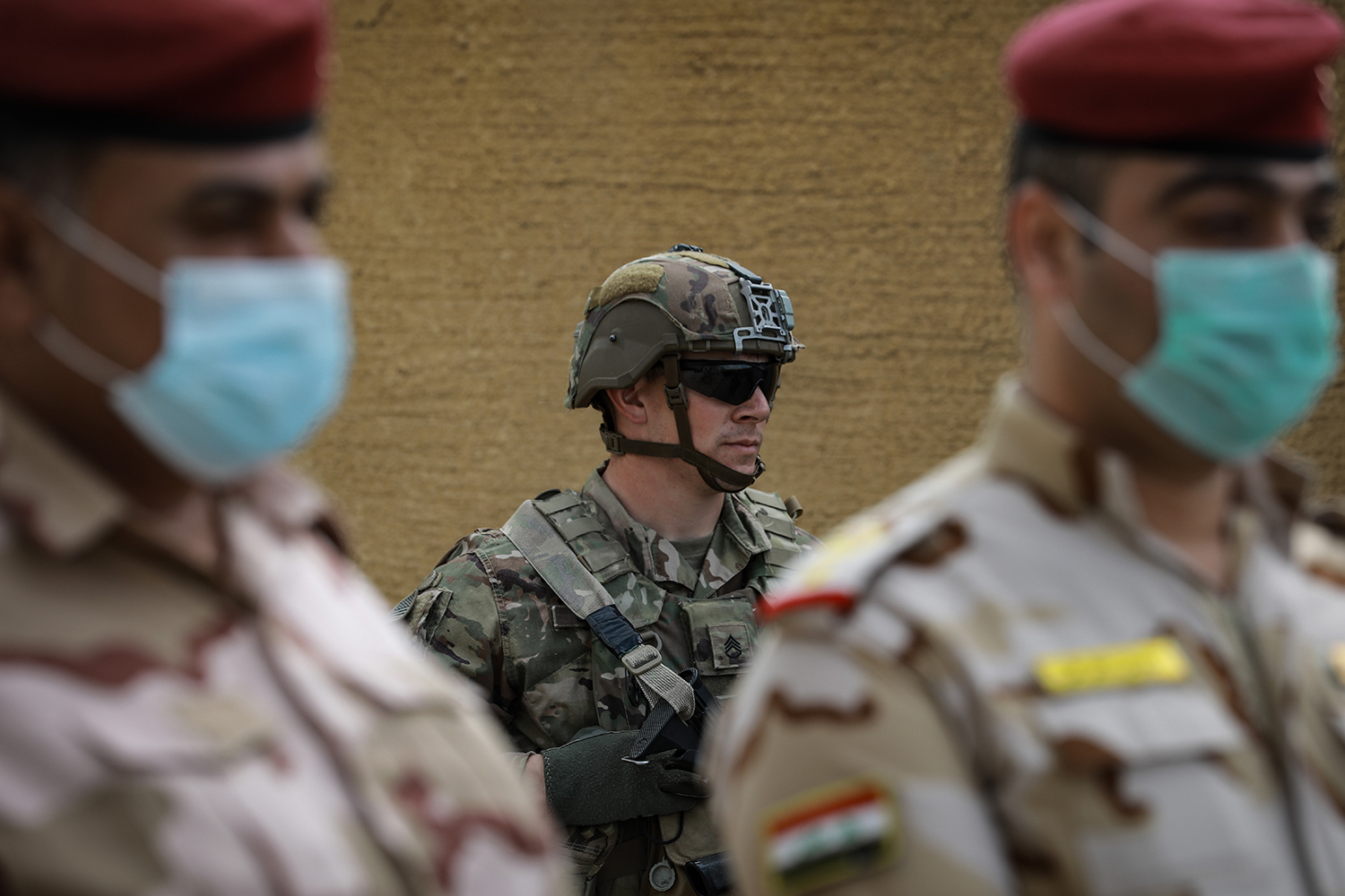 A U.S. soldier stands behind Iraqi soldiers wearing face masks during the handover ceremony of the K1 Air Base near Kirkuk on March 29.